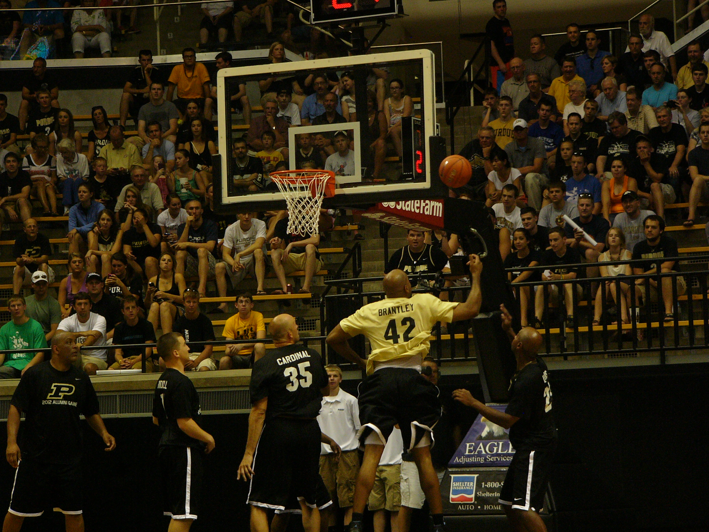Brian Cardinal, No. 35,  looks on as Brandon Brantley goes up strong for a rebound during the Alumni Game.
