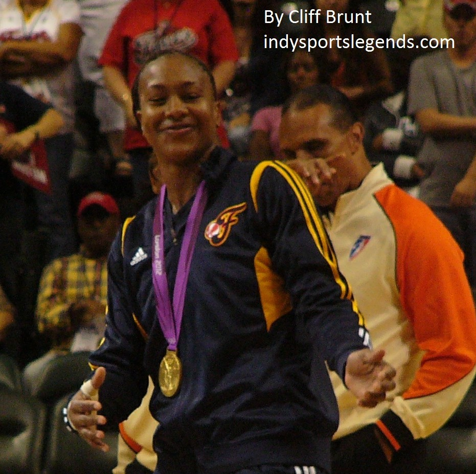 Tamika Catchings poses with her Olympic gold medal.