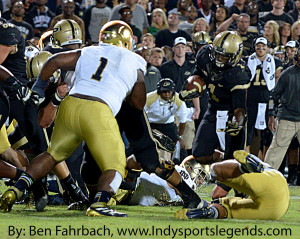 Purdue coach Darrell Hazell watches as Akeem Hunt (1 in black) tries to avoid Notre Dame's Louis Nix III (No. 1 in white).