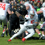Purdue's Bruce Gaston (90) gets ahold of Ohio State quarterback Braxton Miller in 2013. Miller is now a receiver, and the quarterback play has fallen off.